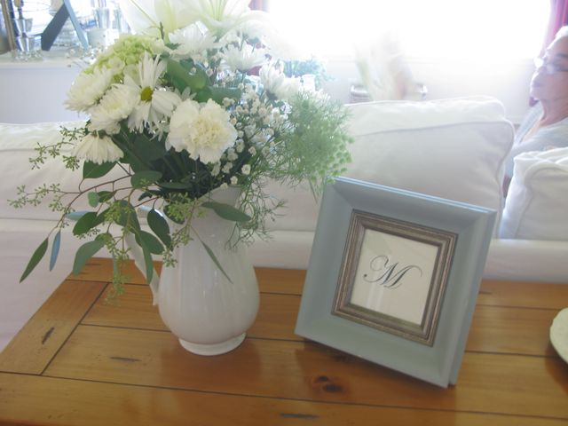 flowers on the sofa table with a printed M in frame